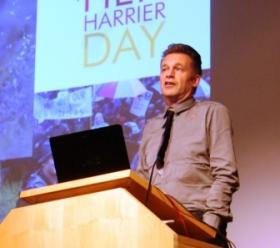 Chris Packham stands behind a lectern during Controversial Conservation.