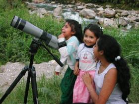 Children watching a hummingbird feeder