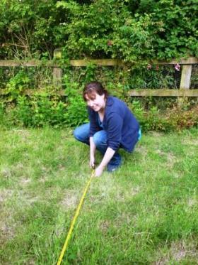 Kelly measures her garden.