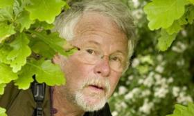 Photograph of Bill Oddie looking out from the undergrowth