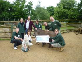 Group photograph of Paradise Wildlife Park staff presenting a cheque to Viv and John Burton.